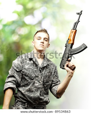 portrait of young soldier holding rifle wearing urban camouflage against a nature background - stock photo