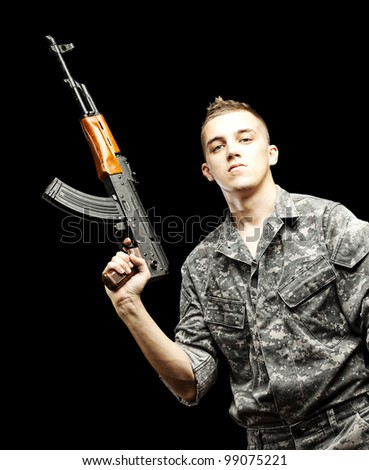 portrait of young soldier holding rifle wearing urban camouflage over black background - stock photo