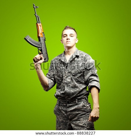 portrait of young soldier holding rifle wearing urban camouflage over green background - stock photo