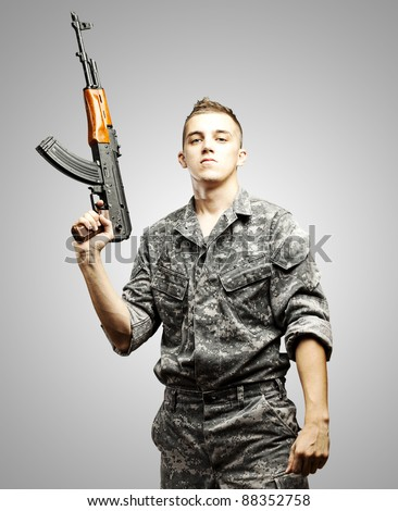 portrait of young soldier holding rifle wearing urban camouflage over grey background - stock photo
