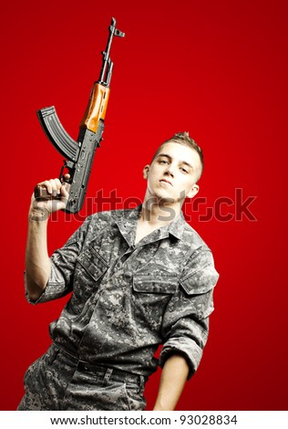 portrait of young soldier holding rifle wearing urban camouflage over red background - stock photo