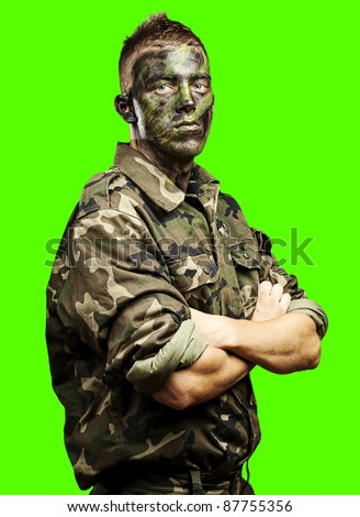 portrait of young soldier painted with jungle camouflage against a removable chroma key background - stock photo