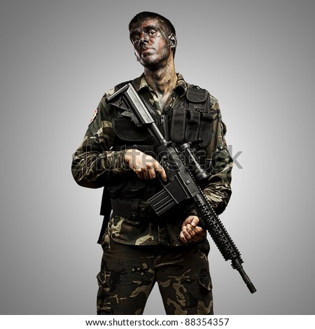 portrait of young soldier painted with jungle camouflage holding riffle over grey background
