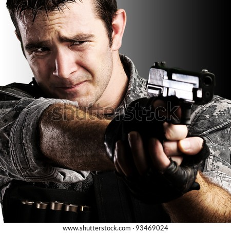 portrait of young soldier pointing with a gun against a black and white background