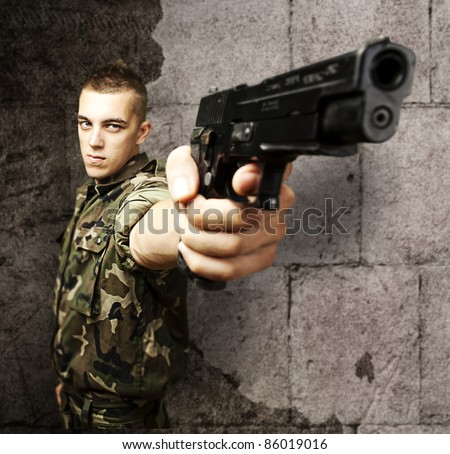 portrait of young soldier pointing with gun against a grunge background - stock photo