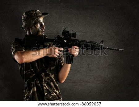 portrait of young soldier pointing with rifle against a grunge wall