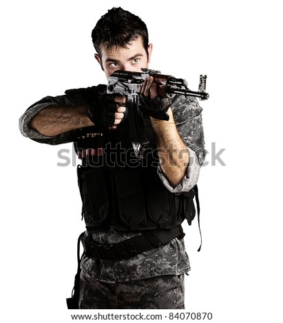 portrait of young soldier pointing with rifle against a white background - stock photo