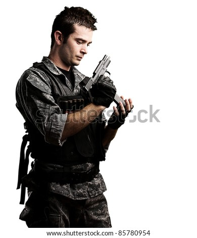 portrait of young soldier reloading his gun against a white background - stock photo