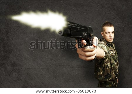 portrait of young soldier shooting with gun against a grunge background - stock photo