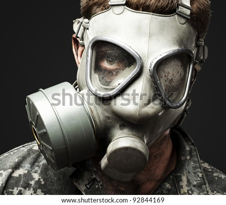 portrait of young soldier wearing gas mask against a black background