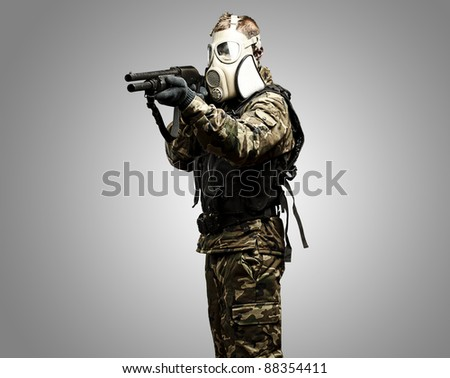 portrait of young soldier with gas mask aiming with shotgun - stock photo