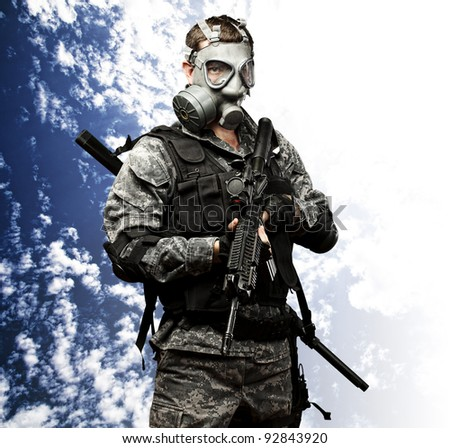 portrait of young soldier with gas mask and rifle against a cloudy sky background