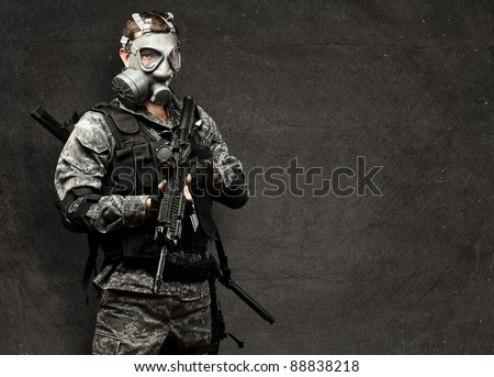portrait of young soldier with gas mask and rifle against a grunge background - stock photo