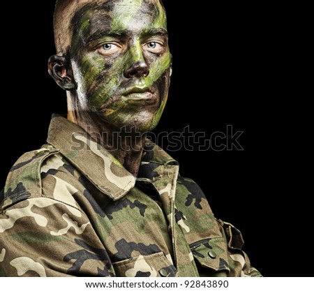 portrait of young soldier with jungle camouflage paint on a black background - stock photo