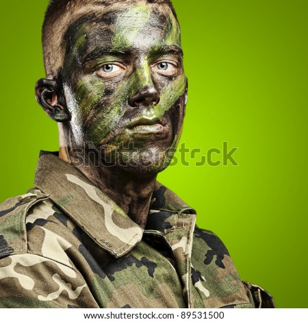 portrait of young soldier with jungle camouflage paint on a green background - stock photo