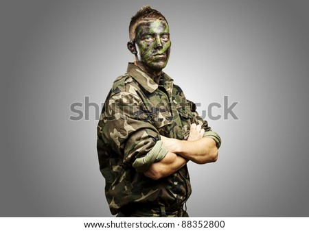 portrait of young soldier with jungle camouflage paint on a grey background - stock photo