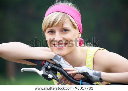 Portrait of young sports woman on bicycle on summer background - stock photo