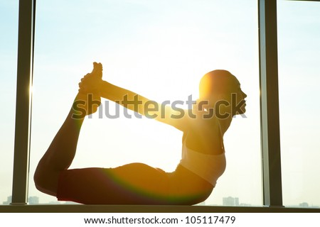 Portrait of young sporty girl doing stretching exercise - stock photo