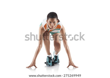 Portrait of young sporty woman at starting block of race isolated over white background - stock photo