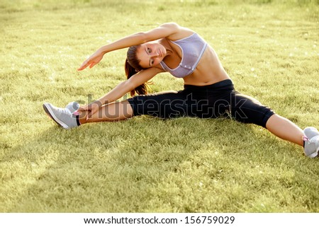 Portrait of Young Sporty Woman Doing Stretching Exercise. Athletic Workout.