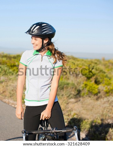 portrait of young sporty woman with bicycle outdoor - stock photo