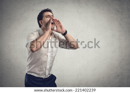 Portrait of young stressed business guy screaming loud in fury.  Male speaker yelling for help. Financial crash or crisis concept.  - stock photo