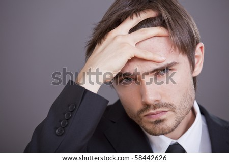 Portrait of young stressed businessman over grey background - stock photo
