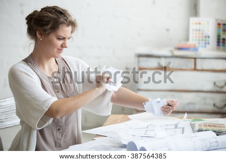 Portrait of young stressed woman sitting at desk in a little office or home wearing smart casual clothing angry with work, ripping documents with frustrated facial expression. Negative human emotions - stock photo