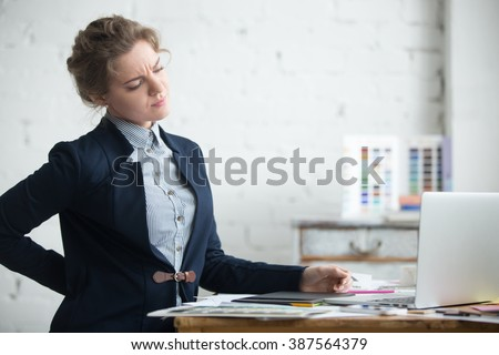 Portrait of young stressed woman sitting at home office desk in front of laptop, touching aching back with pained expression, suffering from backache after working on pc - stock photo