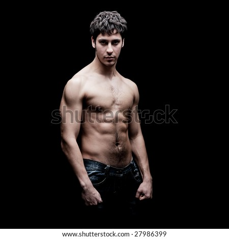 portrait of young strong man against black background - stock photo