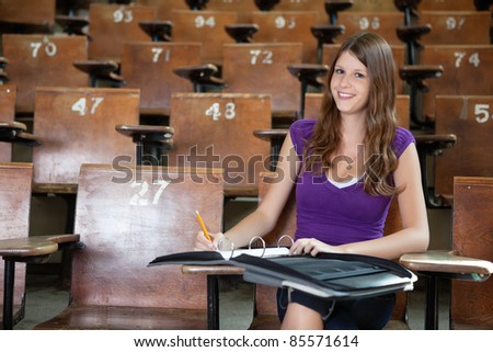 Portrait of young student completing assignment at university - stock photo