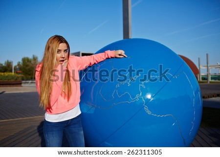 Portrait of young student girl with positive shocking face pointing to the earth globe standing on school campus, science art globe object, female teenager standing near big world globe outdoors - stock photo