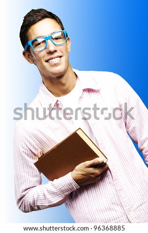 portrait of young student holding a book against a blue background - stock photo