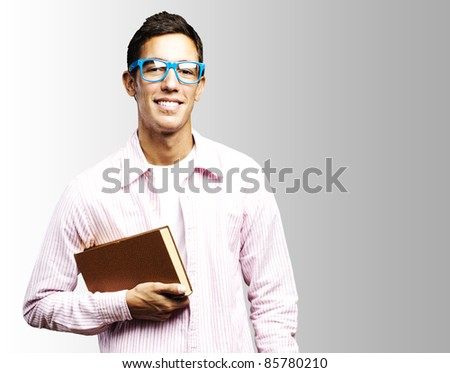 portrait of young student holding a book against a grey background - stock photo