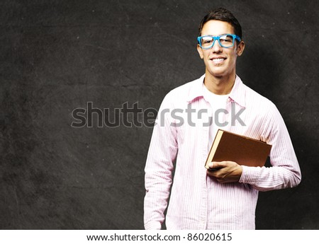 portrait of young student holding a book against a grunge background - stock photo