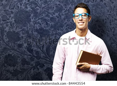portrait of young student holding a book against a vintage background - stock photo