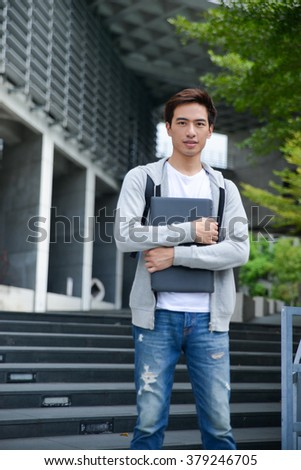 portrait of young student holding tablet awith bag at campus - stock photo