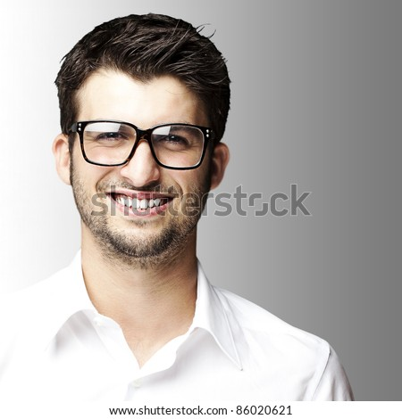 portrait of young student smiling with glasses on grey background - stock photo