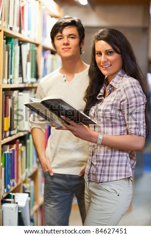 Portrait of young students holding a book in a library - stock photo