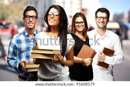 portrait of young students holding books at street - stock photo