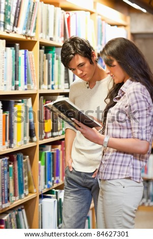 Portrait of young students looking at a book in a library - stock photo