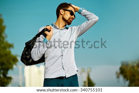 portrait of young stylish confident happy handsome  model man in hipster cloth with bag in the street, life style