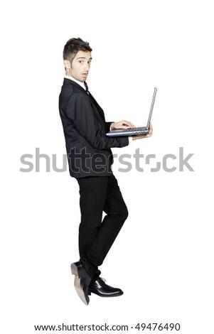 Portrait of young stylish man in tuxedo holding laptop, studio shot - stock photo