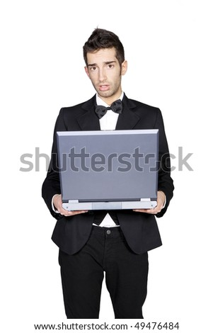 Portrait of young stylish man in tuxedo looking confused and holding laptop, studio shot - stock photo