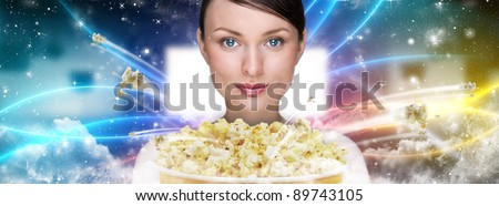 Portrait of young stylish modern woman  watching movie at modern cinema and eating exploding popcorn. - stock photo