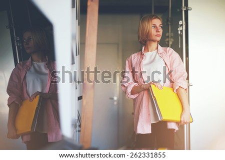 Portrait of young stylish woman holding bright yellow book standing near shelf in home interior, creative female designer with big magazine catalog standing in her studio while focused looking away - stock photo