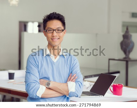 Portrait of young successful businessman in office - stock photo