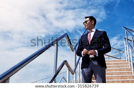 Portrait of young successful director standing with a cigarette against blue sky with copy space,confident asian businessman dressed in formal wear enjoying rest and smoke cigarette outside the office - stock photo