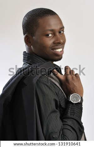 Portrait of young successful fashionable businessman holding jacket over shoulder on grey background - stock photo