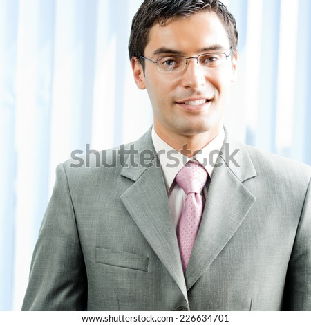 Portrait of young successful smiling businessman at office - stock photo